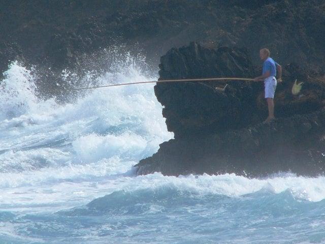 Angler mit Bambusstange bei tobendem Meer