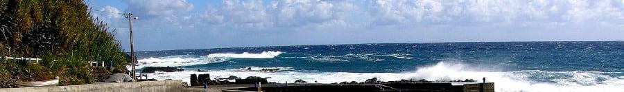 Eine Welle schwappt an die Kaimauer