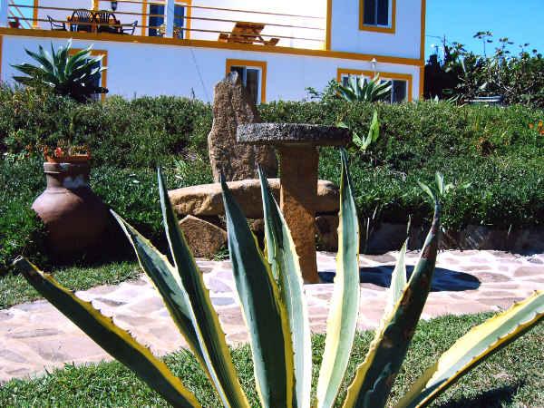 Der Garten mit Sitzplatz und Haus im Hintergrund