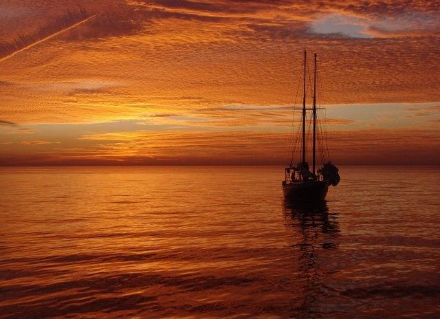 Segelboot auf hoher See im Sonnenuntergang
